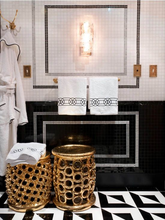 an exquisite black and white bathroom with a geo tile floor, a catchy color block tile wall, refined gold stools