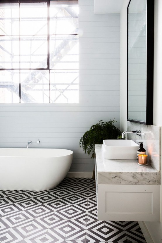 an eclectic bathroom with black and white geometric tiles on the floor, white beadboard walls, a floating vanity with a whiet stone countertop