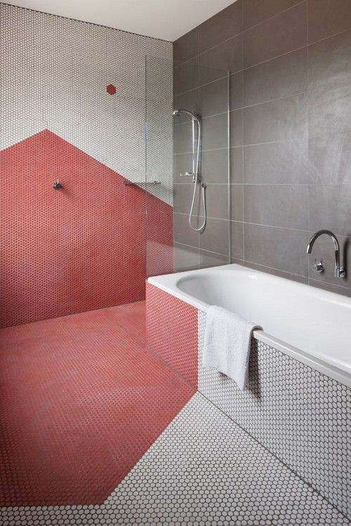a contemporary bathroom with red geometric detailing, white penny tiles and large scale grey ones is very stylish and bold