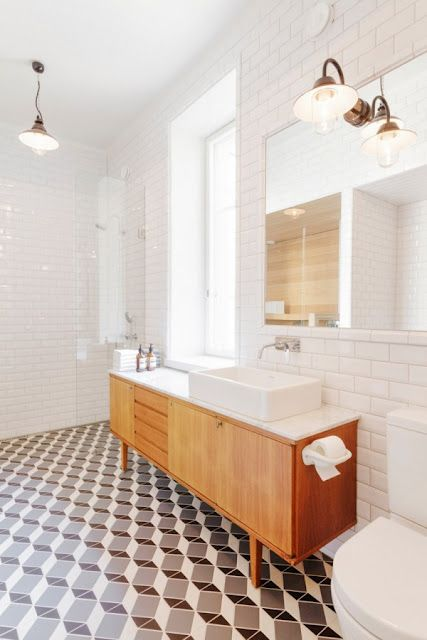 a mid-century modern bathroom with geometric tiles on the floor, white subway tiles on the walls and a wooden vanity with white appliances