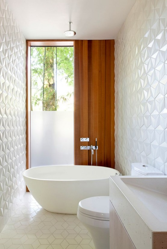 a mid-century modern bathroom with white geometric tiles all over the walls and floor, white appliances is amazing
