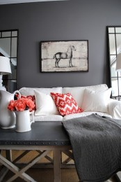 a moody living room with grey walls, a vintage artwork, a white sofa and a grey coffee table and a grey blanket