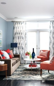 a bright coral, grey and white living room with grey walls, a brown sofa, coral chairs, navy touches, printed textiles