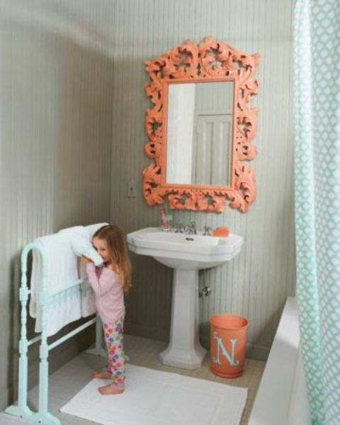 a cute grey and coral bathroom with an ornate mirror, a mint colored stand and a mint curtain