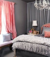 an elegant grey and coral pink bedroom with chic curtains, an upholstered bed, an elegant chandelier and lamp, an upholstered bench