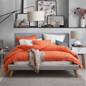 a contemporary bedroom with dove and darker grey walls, furniture and accessories and grey, white and coral bedding