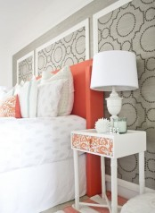 a cheerful grey, white and coral bedroom with a printed wall, a coral bed, bright textiles and a cool white and coral nightstand