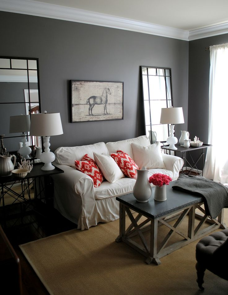 an eclectic grey, white and coral living room with a dark rustic coffee table, bright coral pillows and blooms and vintage mirrors as decor