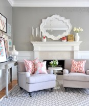 a farmhouse-inspired living room with grey walls, a coffee table, a white fireplace and lots of prints and subtle coral touches