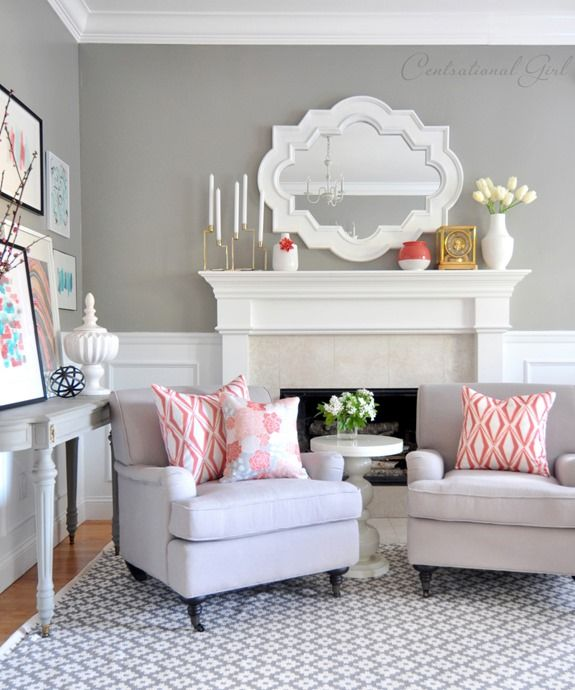 a farmhouse inspired living room with grey walls, a coffee table, a white fireplace and lots of prints and subtle coral touches