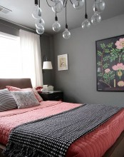 a catchy grey and coral bedroom with a bulb chandelier, a bright artwork, wall lamps and dark nightstands