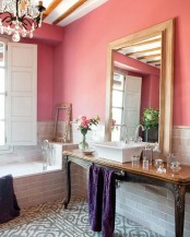 a chic bathroom with a grey floor and walls, coral paint, a large mirror and a crystal chandelier plus a vintage table console