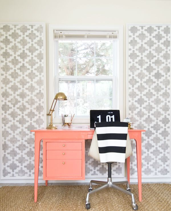 a bright home office nook with grey printed wallpaper, a coral desk, gold touches and a striped chair