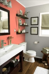 a modern meets rustic bathroom done in coral and grey, with dark stained wooden furniture and white appliances