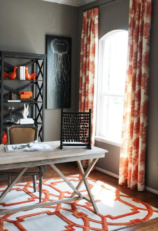 a stylish grey and coral home office with grey walls, a wooden desk, printed textiles, a black shelf and a dark artwork