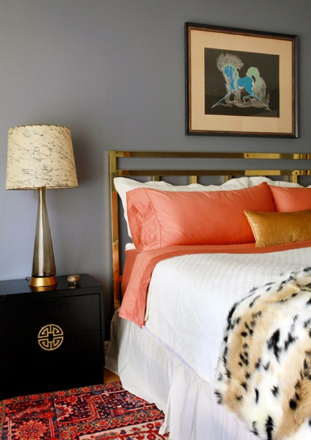 a grey and coral bedroom, a dark nightstand, bright bedding and an artwork and a lamp