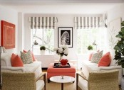 a creamy and coral living room with wicker chairs and grey and white striped shades plus pillows