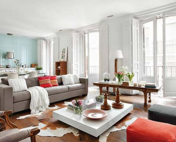 a spacious living room with grey and coral furniture, a white coffee table, a rustic console table, a faux animal skin