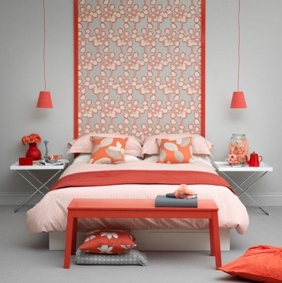 a contemporary grey and coral bedroom with a printed statement wall, grey walls, coral lamps, pillows and a bench and bright bedding