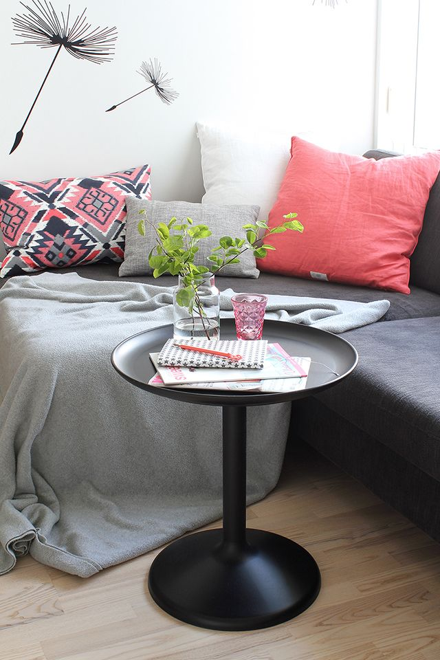 a graphite grey sofa, grey and coral pillows, a black coffee table and fun wallpaper for a stylish living room nook