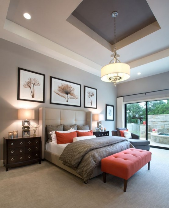a modern bedroom done in light greys, with a coral bench and pillows, dark stained furniture and a glazed wall