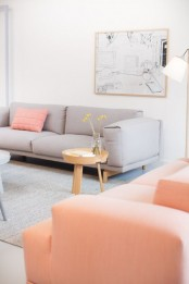 a cute living room with light greys and coral, with an artwork, a coffee table and a floor lamp