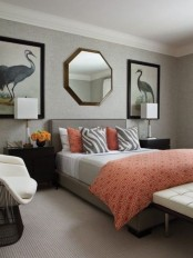 a whimsy bedroom with statement artworks and a geometric mirror, a grey bed, grey and coral bedding and ivory furniture