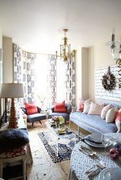 a quirky living room done in light greys, ivory and coral touches, catchy chandeliers, pritned pillows and vintage lamps