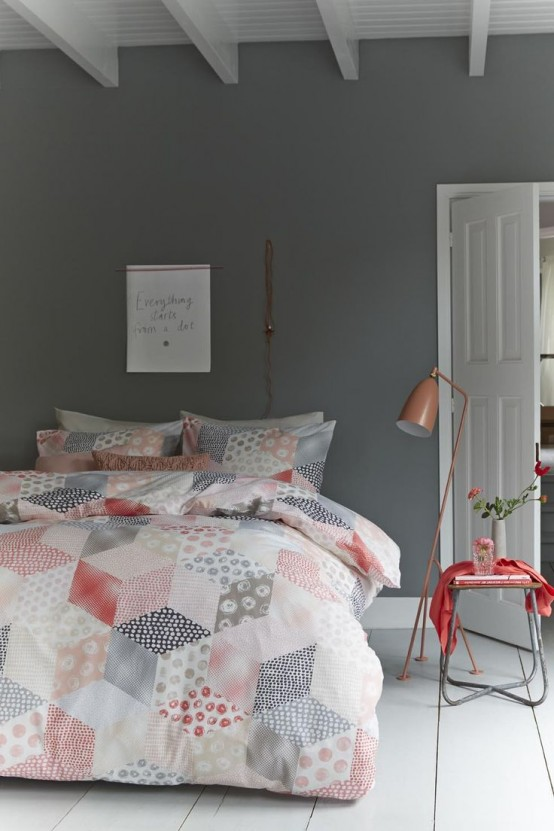 a grey and white bedroom, a small side table with a coral cover, grey, white and coral bedding with a print and a copper lamp