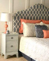 a grey, creamy and coral bedroom with print touches, a whietwashed nightstand, a vintage lamp with a coral base