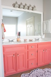 a bright bathroom with dove grey walls, a coral vanity, a white framed mirror and lights