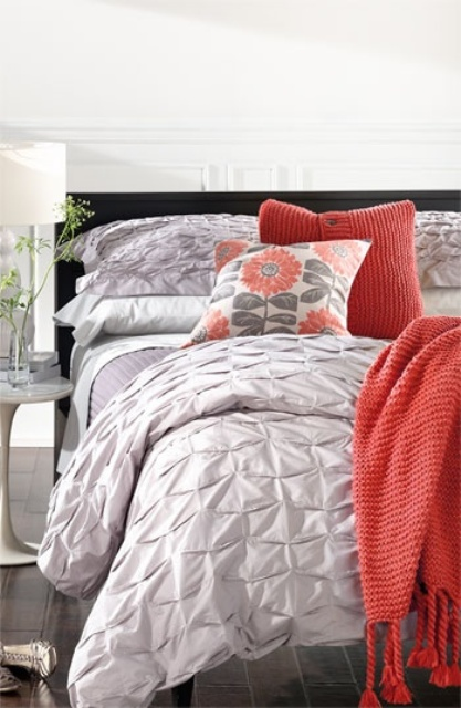 a stylish bedroom with white walls, a grey floor, a black bed, grey, white and coral bedding
