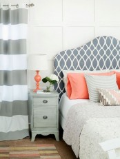 an eclectic bedroom with striped curtains, a printed bed, coral and pink pillows and a whitewashed nightstand