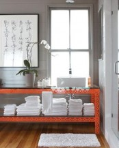 a cool contemporary bathroom done in grey and white, a coral console table with a glass tabletop, an artwork and an orchid