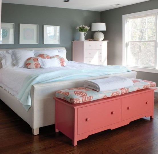 a welcoming bedroom with grey walls, white furniture, a gallery wall, a coral storage bench