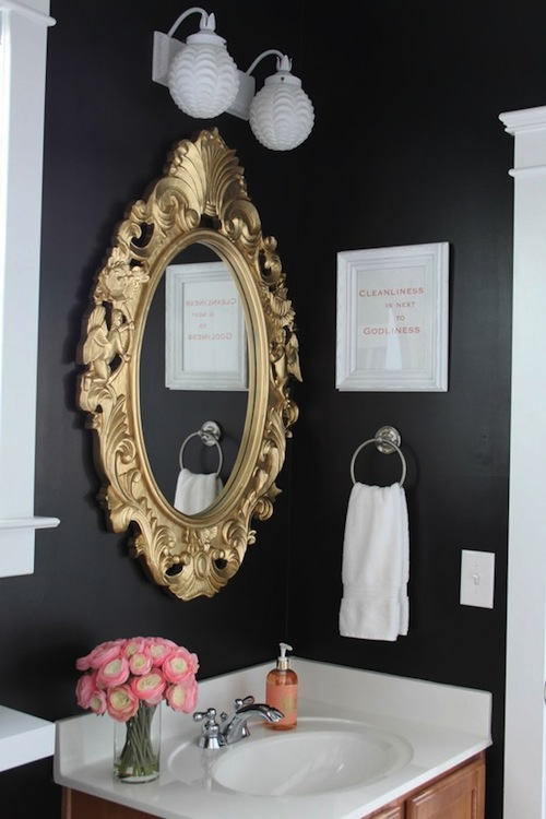 a moody guest toilet done in black and white, with a copper vanity and a mirror in a refined gold mirror frame