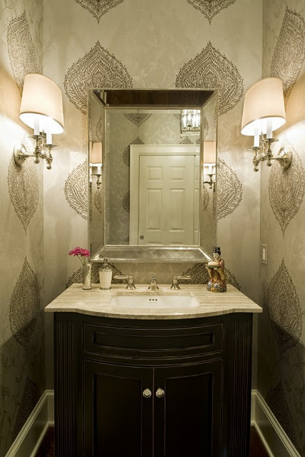 a small neutral guest toilet with printed wallpaper, a dark vanity, a mirror and wall lamps