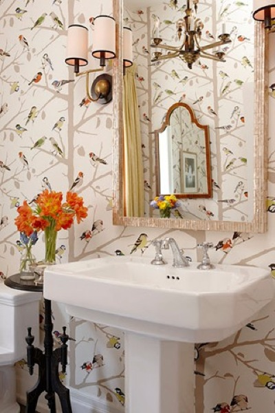 a cheerful guest toilet with a free-standing sink, floral and bird print wallpaper, wall lamps and a framed mirror