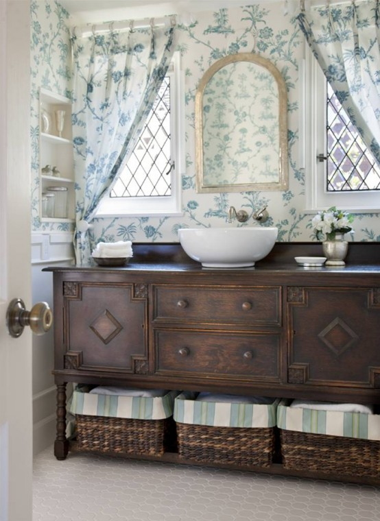 a neutral and elegant guest toilet with a vntage dark-stained vanity, a vessel sink, a mirror and floral print curtains