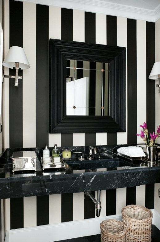 a striped black and white guest toilet with a black framed sink, a stone vanity, wall lamps and baskets