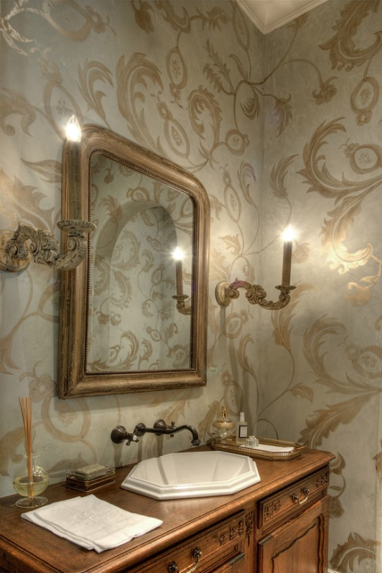 a refined and chic guest toilet with printed wallpaper, a framed mirror, a wooden vanity and wall lamps