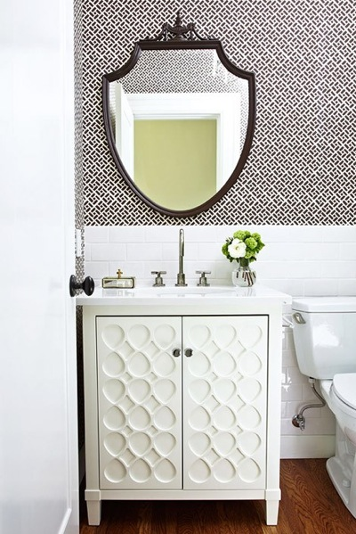 a simple guest toilet with printed wallpaper, white tiles, a white textural vanity and a mirror in a dark frame