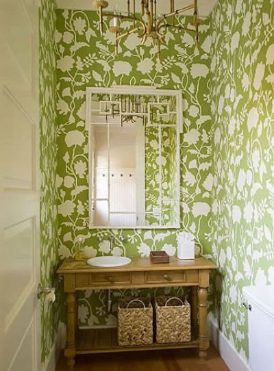 a guest toilet done with green printed wallpaper, a wooden vanity, a chandelier and a mirror
