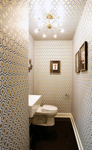 a stylish mid-century modern toilet with geometric wallpaper, a square sink and a sunburst chandelier