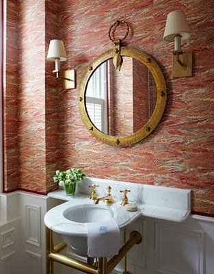 red printed wallpaper, a mirror in an elegant vintage frame, wall lamps and a round sink