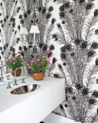 a monochromatic guest toilet with printed wallpaper, a white wall-mounted vanity and a lamp