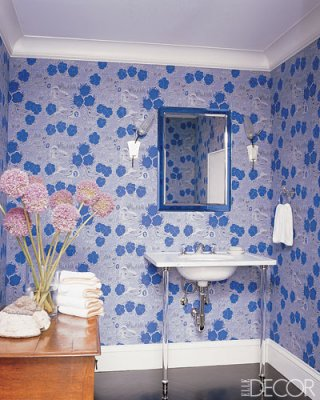 a chic blue and white guest toilet with floral print wallpaper, a wooden storage unit and a sink