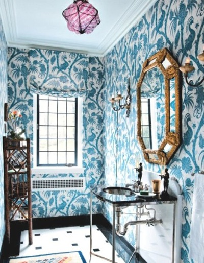 a bright guest toilet done with teal botanical print wallpaper, a delicate vanity with a sink, an exquisite mirror and a storage unit