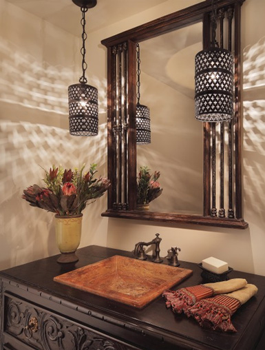 a Moroccan-inspired space with hanging lanterns, a mirror in a wooden frame, a dark-stained wooden vanity
