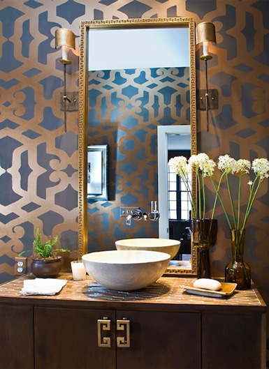 a refined guest toilet with printed wallpaper, a wooden vanity with a vessel sink, wall lamps